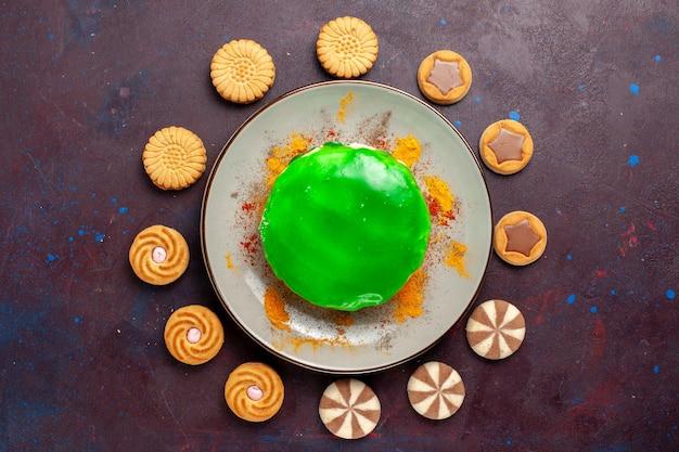 Bovenaanzicht kleine heerlijke cake met verschillende koekjes op het donkere oppervlak