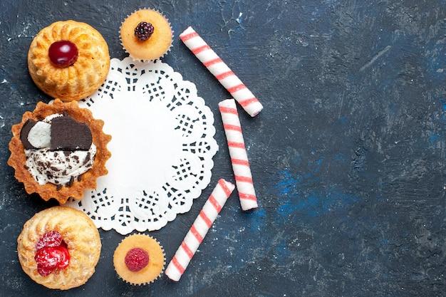 Bovenaanzicht kleine heerlijke cake samen met koekje en roze stok snoepjes fruit op de donkere achtergrond biscuit cake zoet fruit bakken