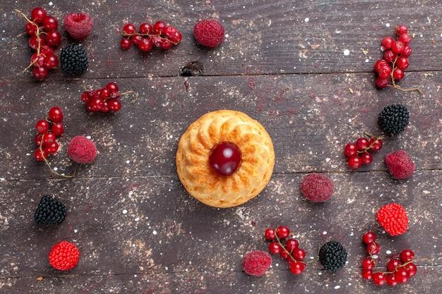 Bovenaanzicht kleine heerlijke cake samen met verschillende gekleurde bessen verspreid over de bruine tafel bessen fruit kleur bak koekje