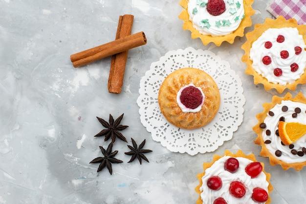 Bovenaanzicht kleine heerlijke cakes met kaneel op het grijze bureau snoepje