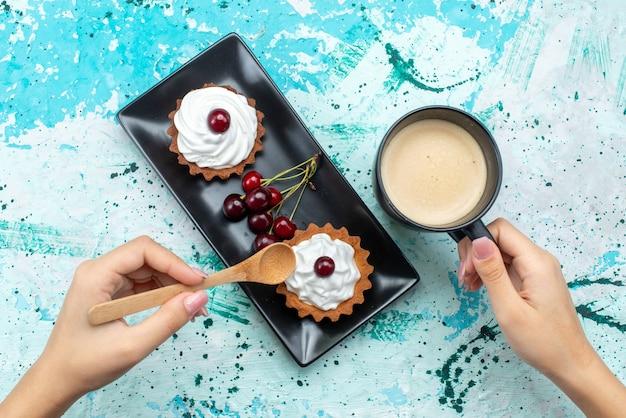 Bovenaanzicht kleine heerlijke cakes met room en fruitmelk op de blauw-lichte tafel cake zoete room fruit bakken