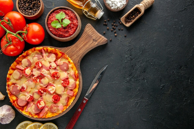 Bovenaanzicht kleine heerlijke pizza met verse rode tomaten op de donkere tafel bezorgvrije ruimte