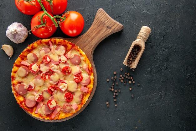 Bovenaanzicht kleine heerlijke pizza met verse rode tomaten op donkere tafel