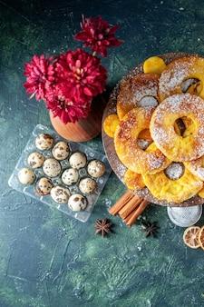 Bovenaanzicht kleine heerlijke taarten in de vorm van een ananasring met melk op een donkere achtergrond, bak taartkoekjes, fruitgebak