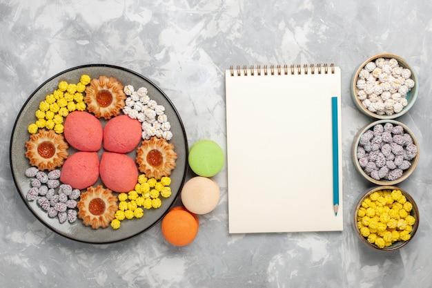 Bovenaanzicht kleine heerlijke taarten met koekjes en snoepjes op witte ondergrond candy sweet biscuit cake pie sugar pie cookies