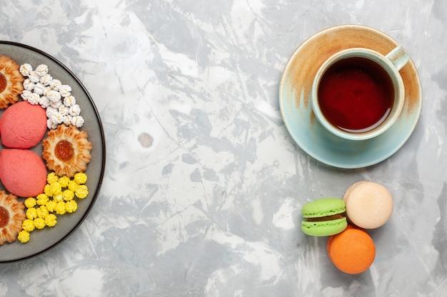 Bovenaanzicht kleine heerlijke taarten met koekjes kopje thee en snoep op het witte oppervlak snoep zoete koektaart taart suikertaart