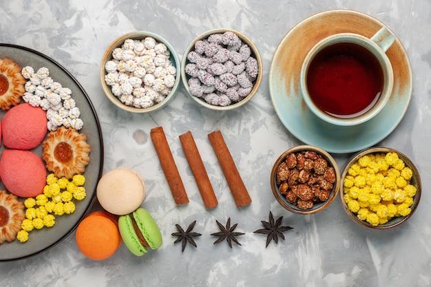 Bovenaanzicht kleine heerlijke taarten met koekjes, thee en snoep op witte ondergrond snoep zoete koektaart taart suiker taartkoekjes