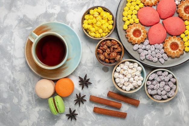 Bovenaanzicht kleine heerlijke taarten met koekjes, thee en snoep op witte ondergrond snoep zoete koektaart taart suikertaart
