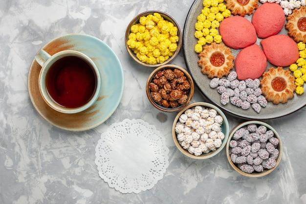 Bovenaanzicht kleine heerlijke taarten met koekjes, thee en snoepjes op wit bureau candy sweet biscuit cake pie sugar pie
