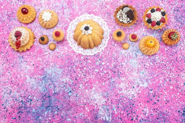 Bovenaanzicht kleine heerlijke taarten met room en bessen op het heldere bureau cake bes zoet