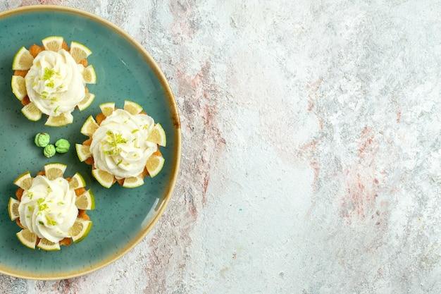Bovenaanzicht kleine heerlijke taarten met room en citroenschijfjes op wit bureau cake biscuit cookie zoete thee suiker