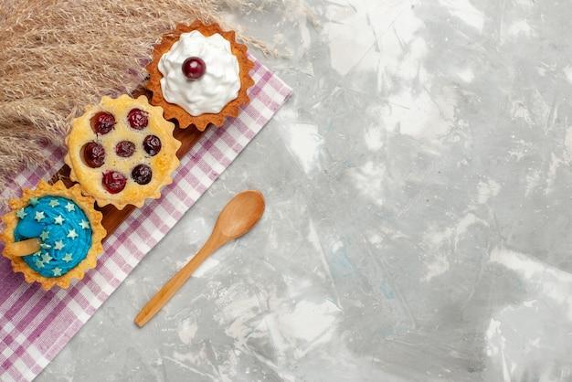 Bovenaanzicht kleine heerlijke taarten met room en fruit op de lichte achtergrond cake zoete room fruit bakken