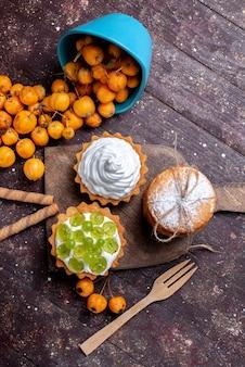 Bovenaanzicht kleine heerlijke taarten met room gesneden druiven koekjes en verse gele kersen op het bruine bureau vers fruit cake biscuit kers