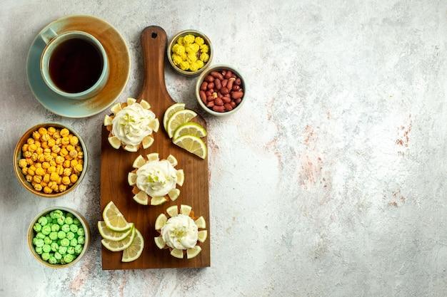Bovenaanzicht kleine heerlijke taarten met schijfjes citroen en snoepjes op wit oppervlak cake biscuit cookie zoete thee crème