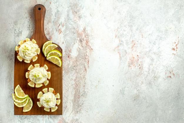 Bovenaanzicht kleine heerlijke taarten met schijfjes citroen op wit oppervlak cake biscuit cookie zoete thee crème