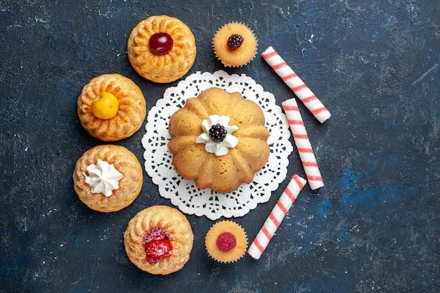 Bovenaanzicht kleine heerlijke taarten samen met roze stok snoepjes op de donkere achtergrond biscuit cake zoete bak