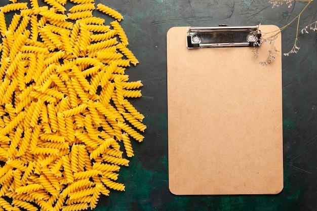 Bovenaanzicht kleine italiaanse pasta met blocnote op het donkere deeg van de achtergrondvoedselmaaltijd van italië