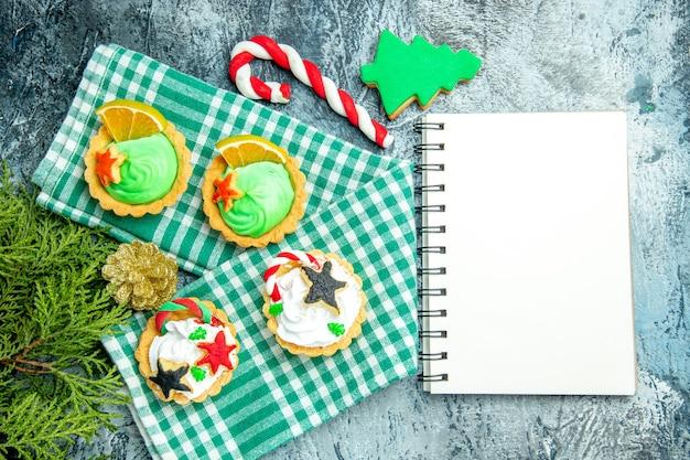 Bovenaanzicht kleine kersttaartjes op tafelkleed pijnboomtakken xmas snoep kladblok op grijze tafel