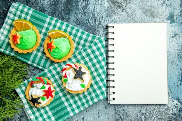 Bovenaanzicht kleine kersttaartjes op tafellaken dennentakken kladblok op grijze tafel