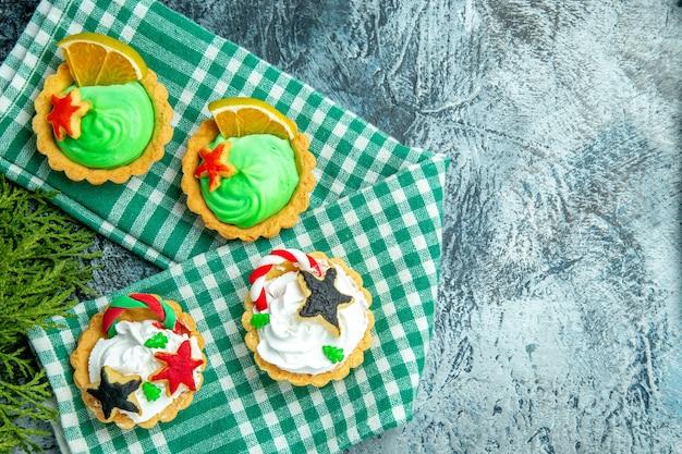 Bovenaanzicht kleine kersttaartjes op tafellaken dennentakken op grijze tafel kopie plaats Gratis Foto