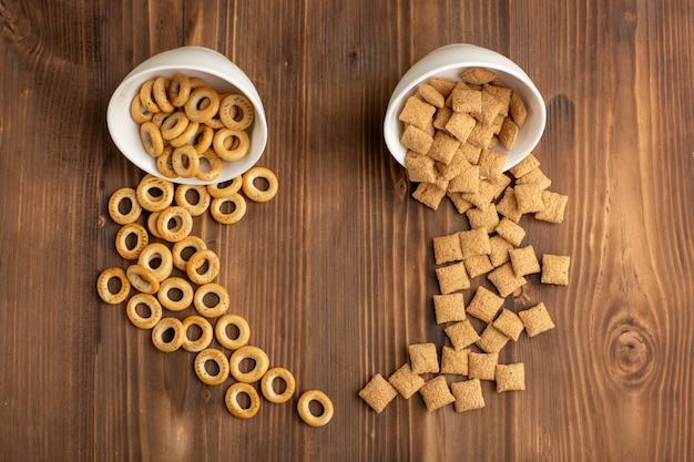 Bovenaanzicht kleine koekjes en crackers op bruin houten bureau