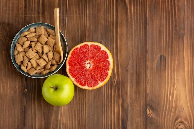 Bovenaanzicht kleine koekjes met grapefruit en appel op het bruine houten bureau