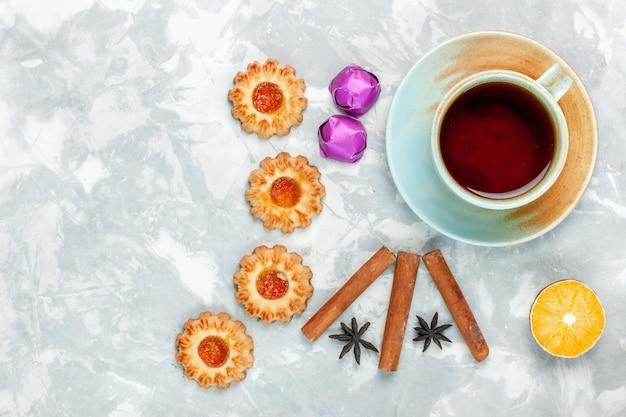 Bovenaanzicht kleine koekjes met kaneel en thee op lichte witte ondergrond