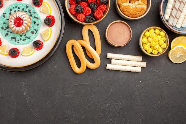 Bovenaanzicht kleine koekjescake met schijfjes citroen en snoepjes op de donkere achtergrondcake, zoet koekje, fruit, citruskoekje