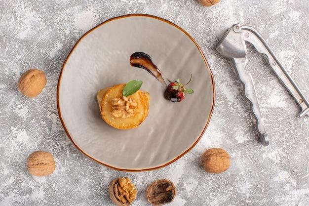 Bovenaanzicht kleine koekjesgebakjes met walnoten op tafel, cake, koekjes, suiker, zoet gebak bakken
