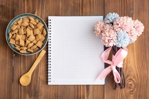 Bovenaanzicht kleine kussenkoekjes met blocnote op bruin bureau