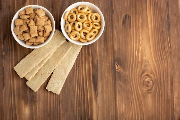 Bovenaanzicht kleine kussenkoekjes met crackers op de bruine vloer