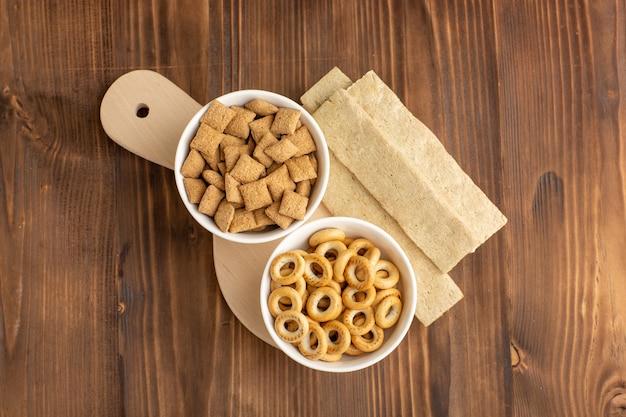 Bovenaanzicht kleine kussenkoekjes met crackers op het bruine bureau