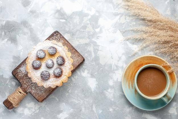 Bovenaanzicht kleine lekkere cake met fruit suiker gepoederd met melkkoffie op licht bureau cake biscuit cake zoete suiker