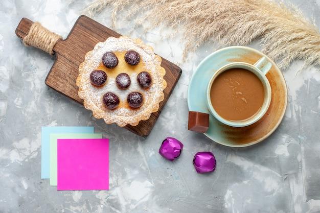 Bovenaanzicht kleine lekkere cake met fruit suiker gepoederd samen met melkkoffie op licht bureau cake koekje cake zoet