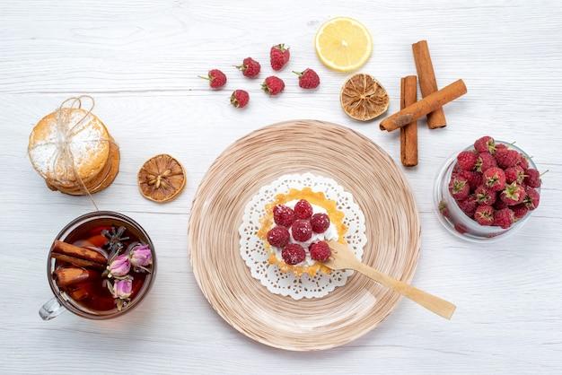 Bovenaanzicht kleine lekkere cake met room en frambozen samen met sandwichkoekjes kaneel thee op de lichtwitte tafel fruit bessen cake koekje zoet