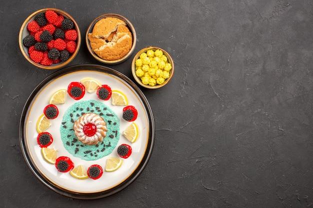 Bovenaanzicht kleine lekkere cake met schijfjes citroen en snoepjes op de donkere achtergrond biscuit cake fruit citrus koekje zoet