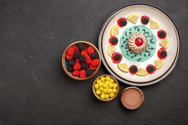 Bovenaanzicht kleine lekkere cake met schijfjes citroen en snoepjes op donkere achtergrond, fruit, citruskoekjeskoekje, zoet