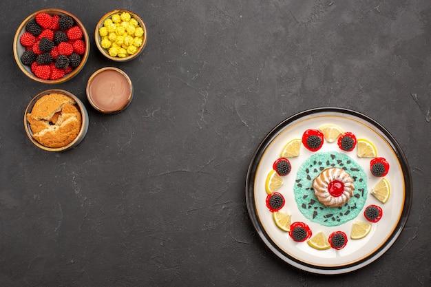 Bovenaanzicht kleine lekkere cake met schijfjes citroen en zoete confitures op donkere achtergrond biscuit fruit citrus zoete cake cookie