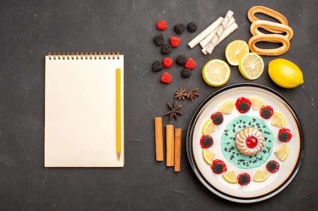 Bovenaanzicht kleine lekkere cake met schijfjes citroen op donkere achtergrond biscuit fruit citrus zoete cake cookies