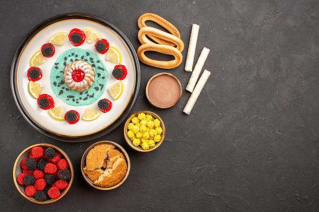 Bovenaanzicht kleine lekkere cake met snoep en schijfjes citroen op donkere achtergrond cake biscuit fruit citrus zoet koekje