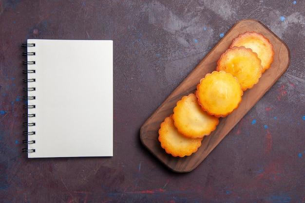 Bovenaanzicht kleine lekkere taarten die op elkaar zijn bekleed op een donkere ondergrond, zoete taartkoekjeskoekjestheecake