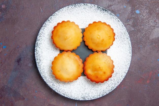 Bovenaanzicht kleine lekkere taarten in plaat op donkere oppervlakte, zoete taartkoekjeskoekjes, theecake