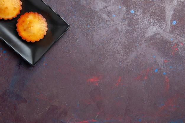Bovenaanzicht kleine lekkere taarten in zwarte cakevorm op donkere bureautaartkoekje, zoete koekjestheecake