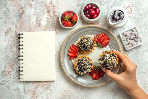 Bovenaanzicht kleine lekkere taarten met aardbeien en snoepjes op witte oppervlakte viering thee zoete biscuit suiker taart crème