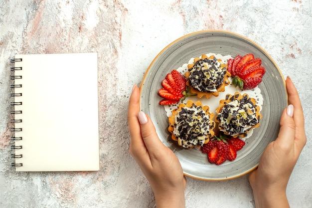 Bovenaanzicht kleine lekkere taarten met aardbeien op witte bureau verjaardagsviering zoete koekjescake