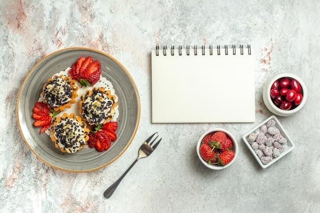 Bovenaanzicht kleine lekkere taarten met aardbeien op witte oppervlakte verjaardagsviering zoete koekjestaart