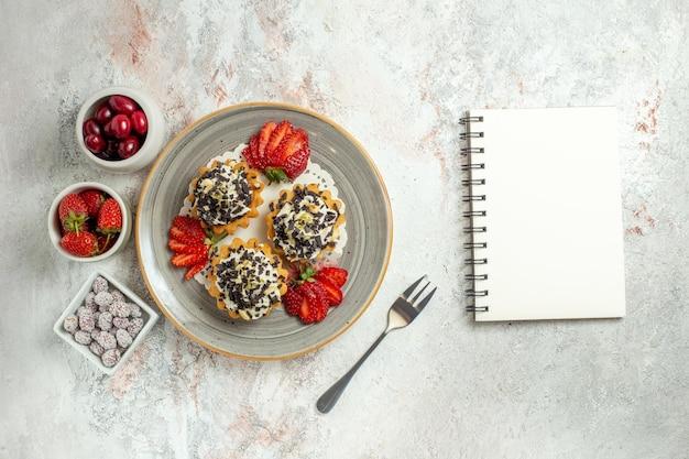 Bovenaanzicht kleine lekkere taarten met room en aardbeien op witte bureau verjaardagsviering zoete koekjescake sweet