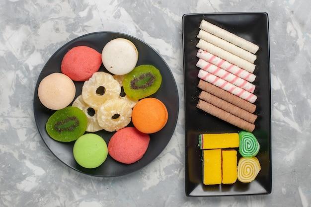 Bovenaanzicht kleine pijp koekjes met marmelade en kleine cakes op witte achtergrond cookie biscuit suiker zoete cake taart