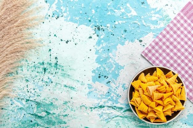 Bovenaanzicht kleine pittige chips in donkere plaat op lichtblauwe achtergrond chips snack kleur scherpe calorie