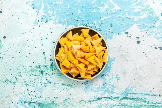 Bovenaanzicht kleine pittige chips in plaat op de lichtblauwe achtergrond chips snack kleur knapperig